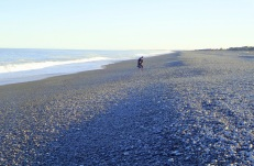 A beach full of stones, the largest above the high tide mark, the smallest closer to the surfline