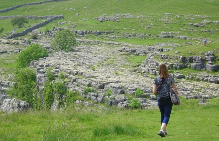 Petra walking down towards the top of Malham Cove, towards the limestone pavement
