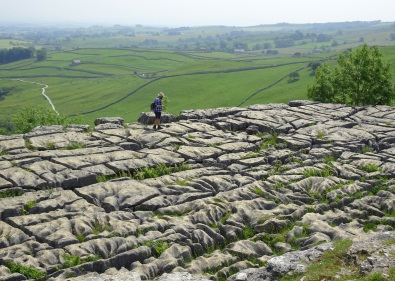 A man near the edge of the limestone pavement at the top of Malham Cove