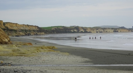 Horse riders and horse-drawn wagon on Gemstone beach.