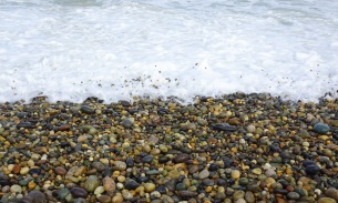 The incoming wave dislodges stones, tossing them in the air and pushing them up and down and along the beach