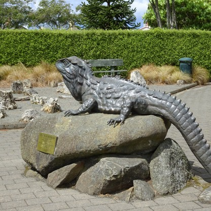 Tuatara statue, with petrified wood in background, sited outside the entrance to the Southland Museum, Invercargill