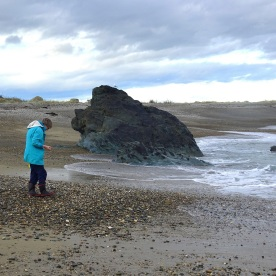 My sister Helen collecting stones at the Back Beach, Riverton, on a rough day
