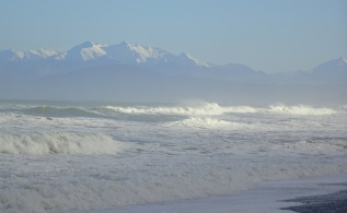 The snow-capped mountains of Eastern Fiordland, from Gemstone Beach. A wild sea generated some powerful waves.