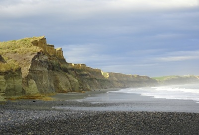 The cliffs to the left of the carpark. Stones in the foreground.