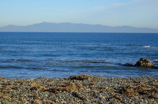 Looking from the Back Beach across a calm Foveaux Strait to Rakiura/Stewart Island.